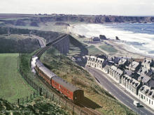 At a sedate 25mph, a class 26 heads for Portknockie in the distance, although it's 7 May 1966 and the sun is turning the coaches into greenhouses.